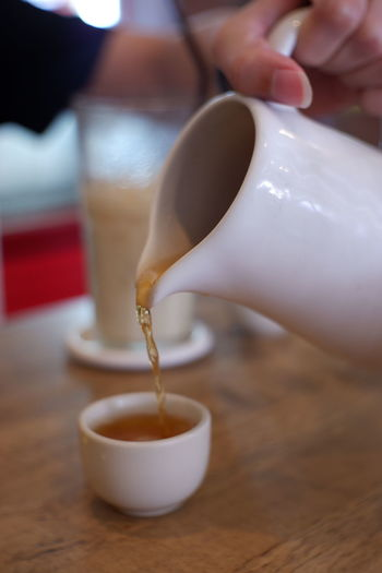 Close-up of hand holding tea cup on table