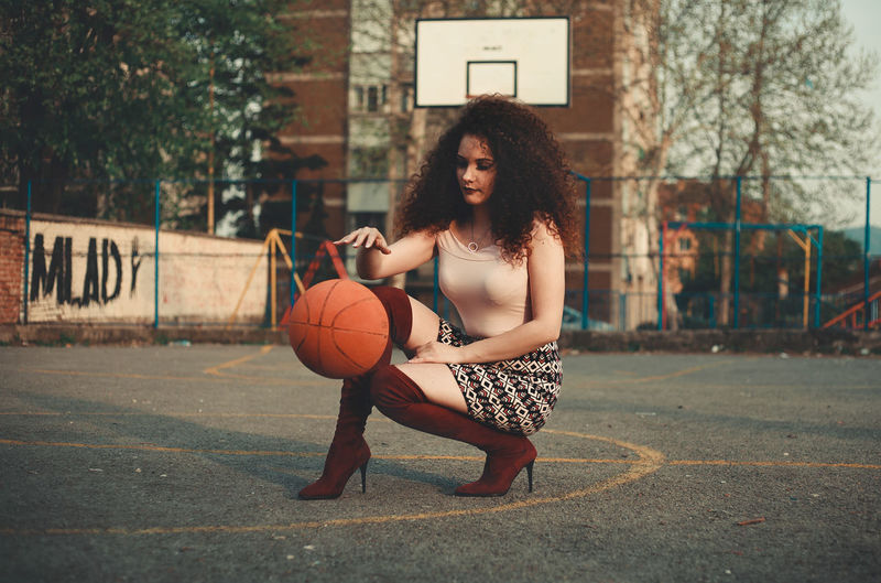 Beautiful young woman playing with basketball on court