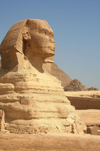 The sphinx and pyramid against clear blue sky