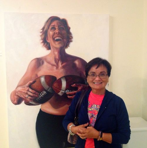 "Standing next to a ""Chick with Balls"" painting by Judy Takács of her unsung female heroes at the BayArts In BayVillage OH."