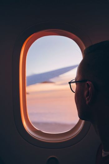 Close-up of man looking through airplane window