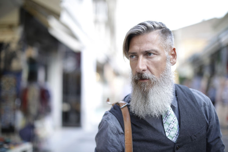 Mature Man With Beard Looking Away While Standing Outdoors