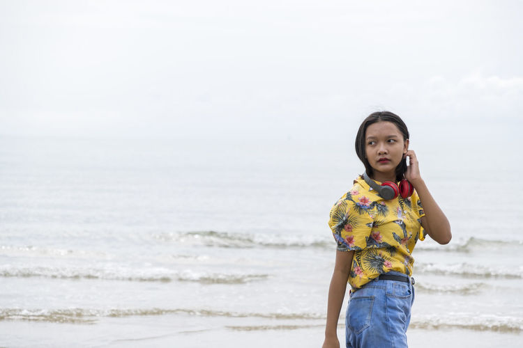Asian young giel listen to the music at the beautiful sea.