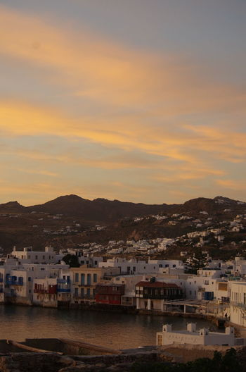 Townscape by sea against sky during sunset