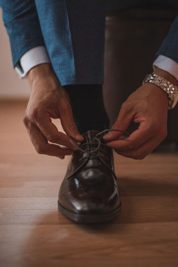 Low section of man tying shoe lace