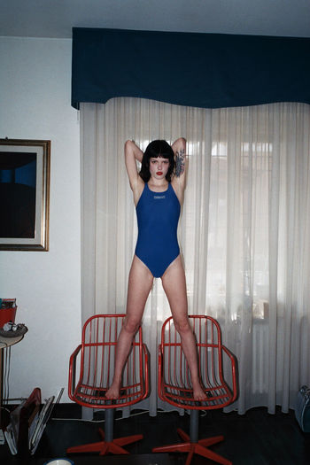 Portrait of young woman standing on chair at home