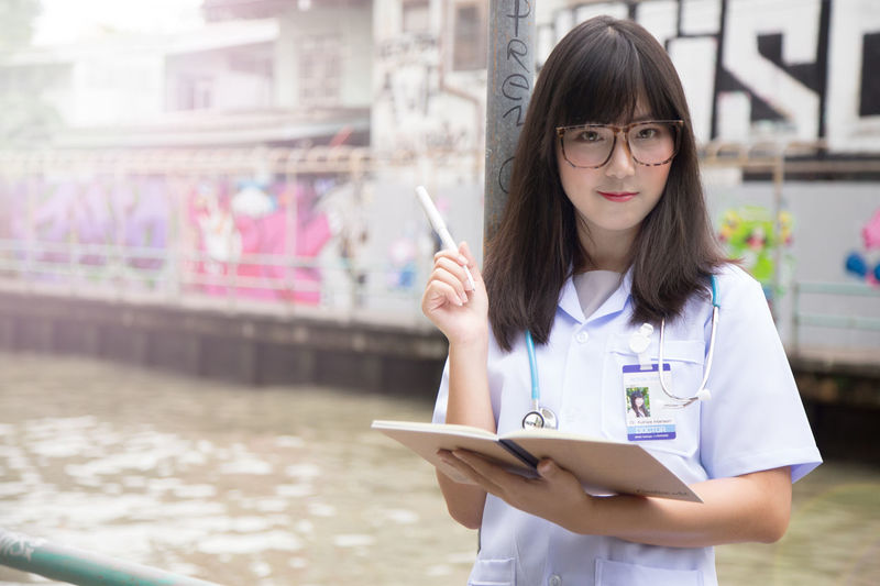 Portrait Of Female Doctor Holding Book While Standing Outdoors