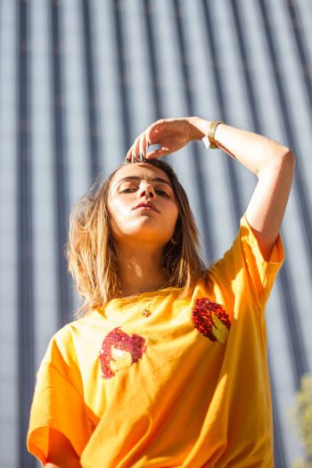 Young woman posing on the street wearing a yellow shirt while the sun is shining. Beautiful Casual City Fashion Happy Shining Sunny Vogue Woman Attractive Enjoy Female Girl Hipster Model One Person Portrait Posing Pretty Street Style Summer Sun Urban Yellow