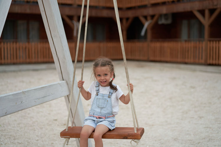 Portrait of happy girl sitting on swing outdoors