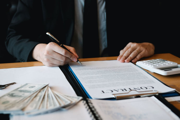 Midsection of businessman analyzing contract on table