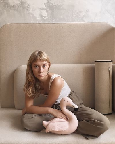 Portrait of woman sitting against wall at home