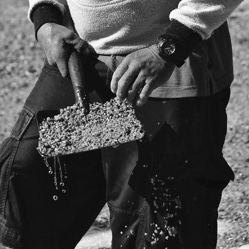 Man holding sand in shovel at beach