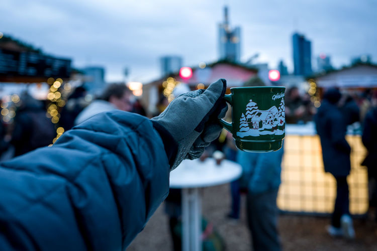 Frankfurt Christmas Market with spiced wine cup and Skyline in background. Christmas Skyline Architecture Building Exterior Built Structure Camera - Photographic Equipment City Close-up Coin-operated Binoculars Day Focus On Foreground Human Body Part Human Hand Low Section Men One Person Outdoors People Photographing Photography Themes Real People Sky Spicedwine Technology Wine