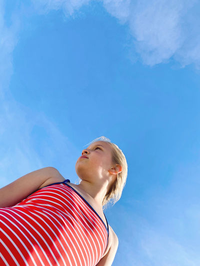 Low angle portrait of woman looking at blue sky