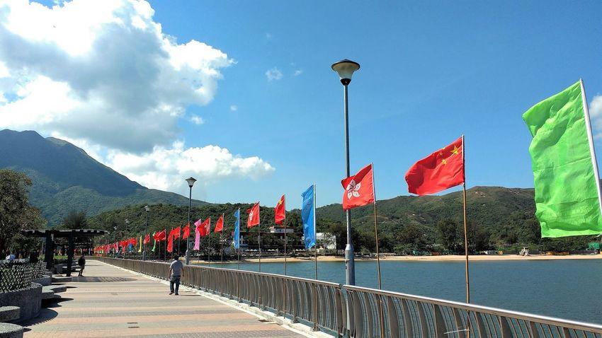 Chinese Flag Hong Kong Flag Lantau Island Mui Wo Promenade Silvermine Bay Bay Beach Blue Sky Clouds Flags Mountain Outdoors Patriotism Sea Seaside Sky Water Waterfront