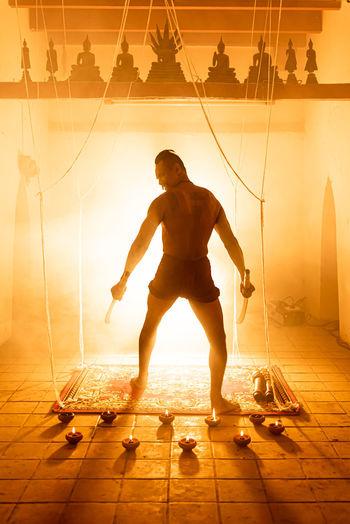 Full length of shirtless man standing against illuminated orange sky