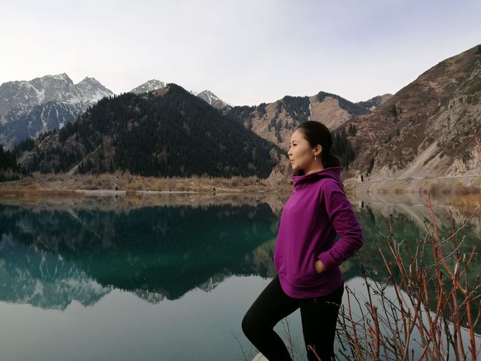 Side View Of Young Woman Standing By Lake Against Mountains