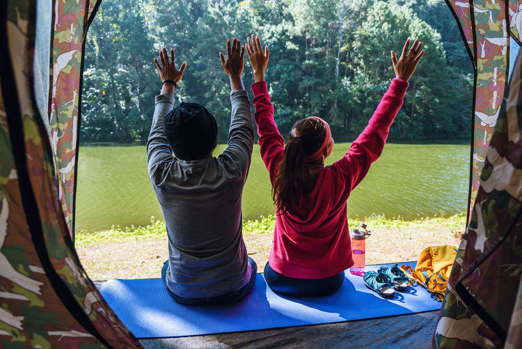 Rear view of people sitting on mat by lake