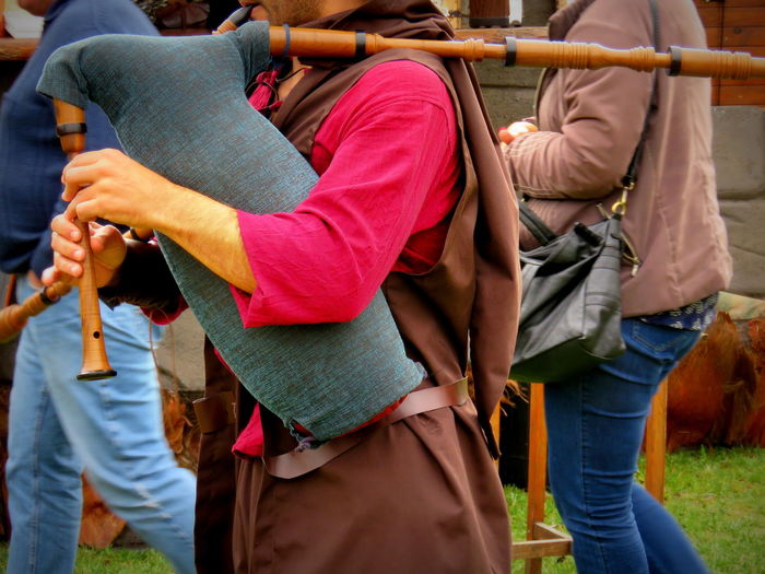 Midsection Of Person Playing Bagpiper During Medieval Fair