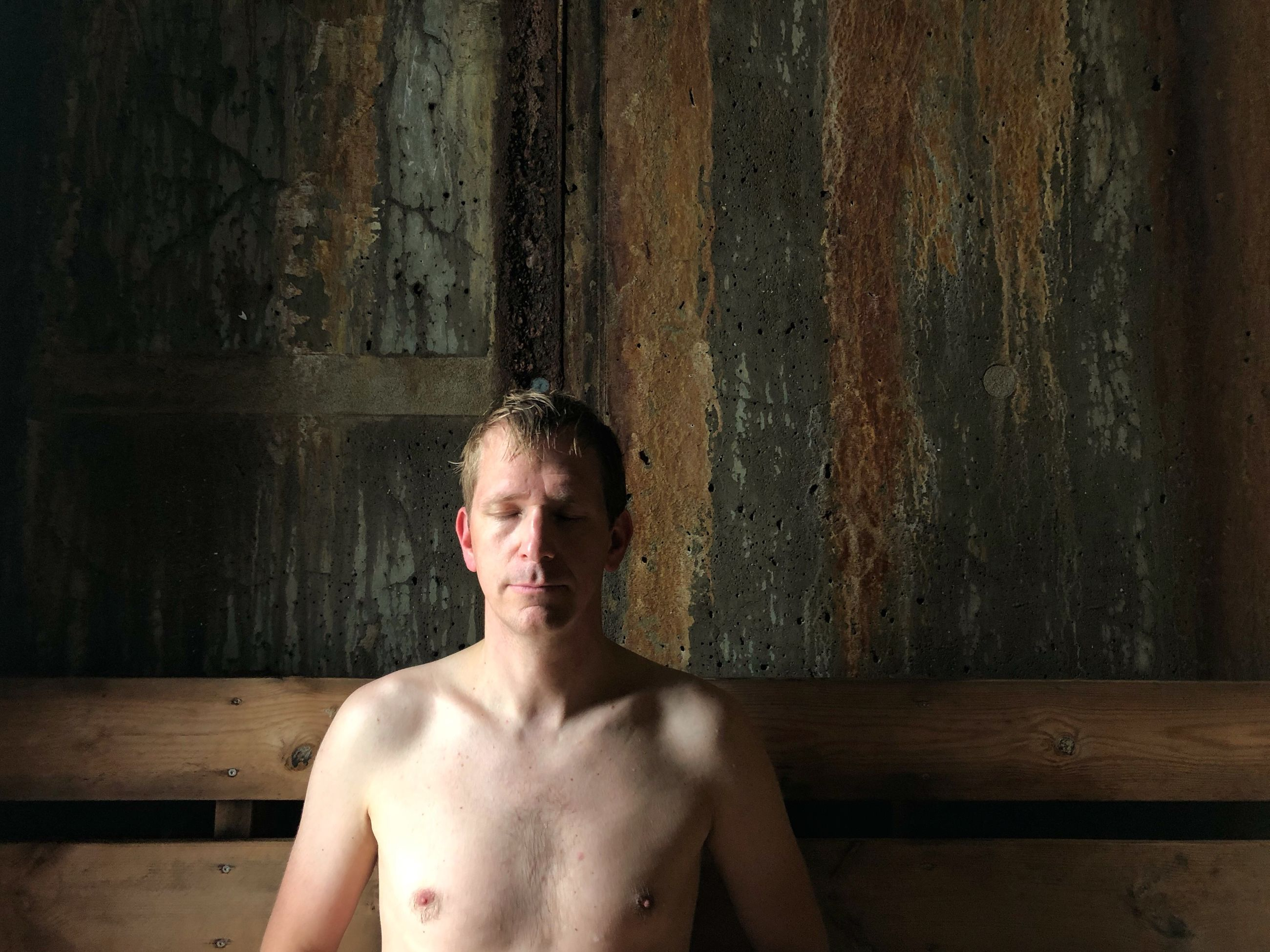 shirtless, one person, real people, lifestyles, portrait, front view, young adult, looking at camera, indoors, leisure activity, standing, young men, wall - building feature, adult, headshot, waist up, wood - material, males, chest, contemplation