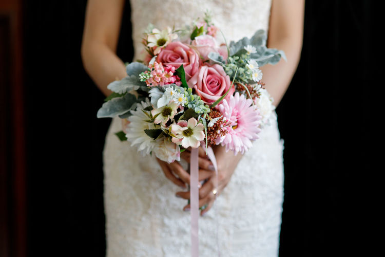 Midsection of bride holding bouquet against black background