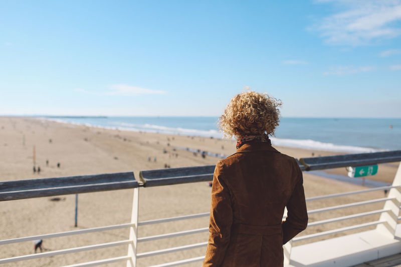 Rear view of woman standing by railing on scheveningen pier at beach against sky