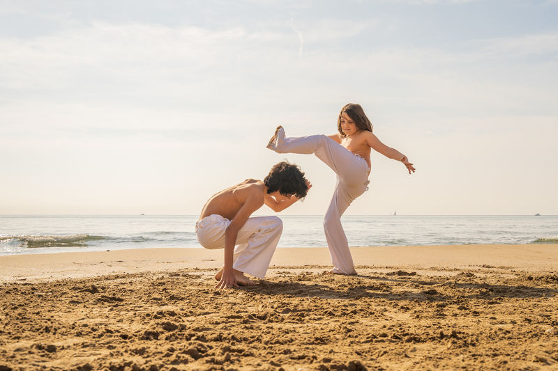 Full length of girl and boy practicing karate at beach against sky
