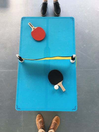 Low section of sports players standing by table tennis