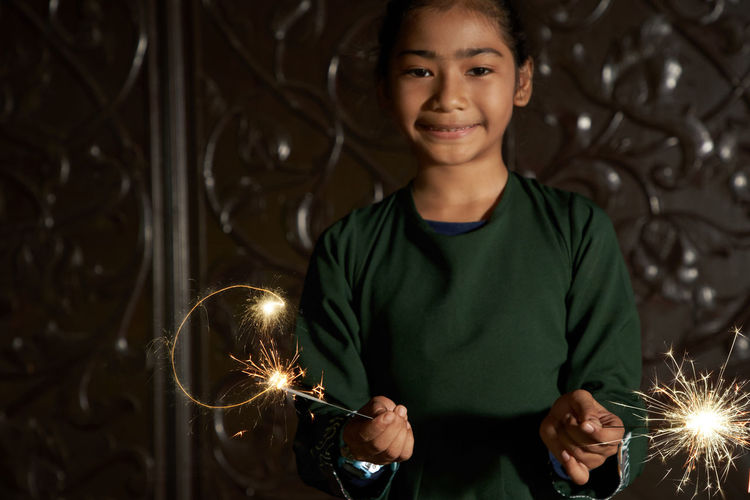 Portrait of malay girl holding sparkler during ramadan festival