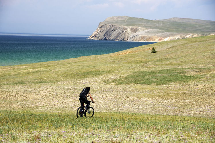 Rear view of man riding bicycle on land against sky