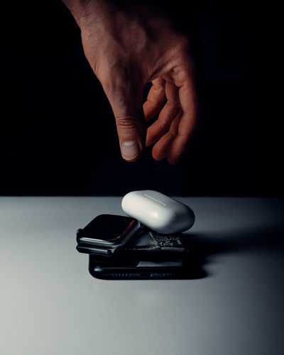 Close-up of human hand on table against black background