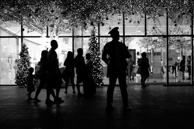 Silhouette people on city street during christmas