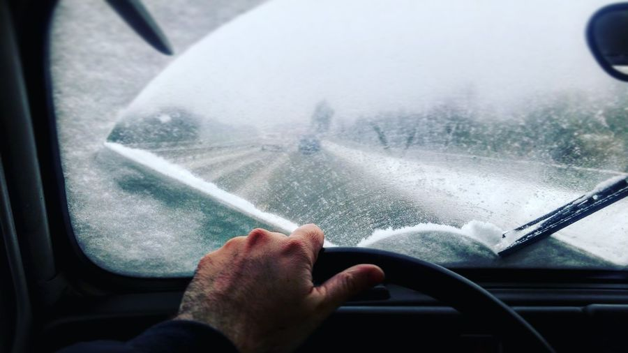 Cropped image of man driving car during winter