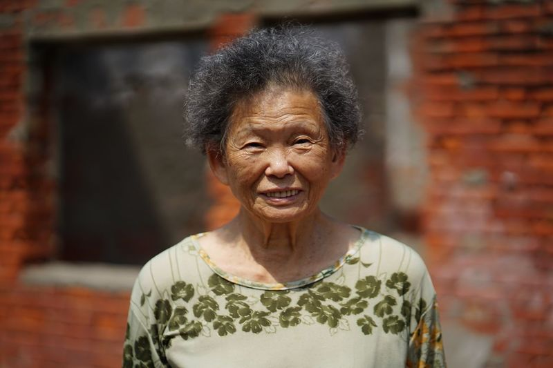 Portrait Of Smiling Senior Woman Standing Against Building