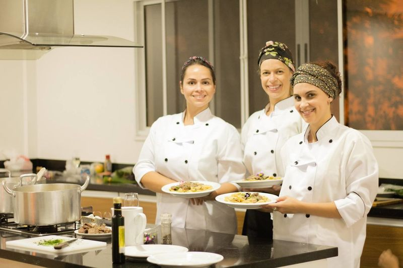 Portrait Of Happy Female Chefs Holding Pasta In Plates While Standing In Commercial Kitchen