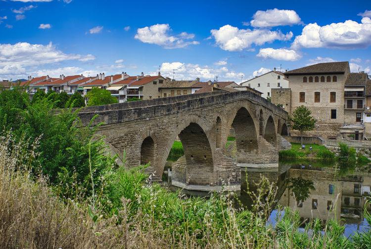Arch bridge by buildings against sky in city