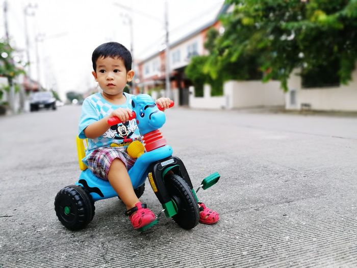 Boy sitting in bicycle on road