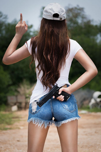 Standing woman holding a gun hidden behind Brown Hair Casual Clothing Day Fashion Focus On Foreground Hair Hairstyle Hot Pants Human Arm Leisure Activity Lifestyles Long Hair Nature One Person Outdoors Real People Rear View Shorts Standing Three Quarter Length Women Young Adult Young Women