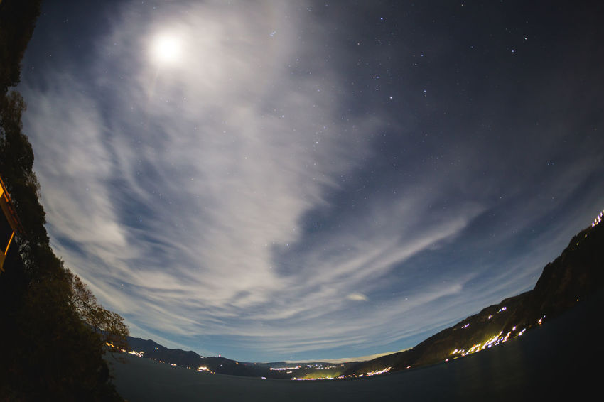 Fisheye view of moonlight and clouds over Lake Atitlan in Guatemala, Central America. Perspectives On Nature Astronomy Beauty In Nature Constellation Fish-eye Lens Galaxy Illuminated Landscape Moon Mountain Nature Night No People Outdoors Scenics Sky Star - Space Star Field Star Trail Starry Tranquil Scene Tranquility