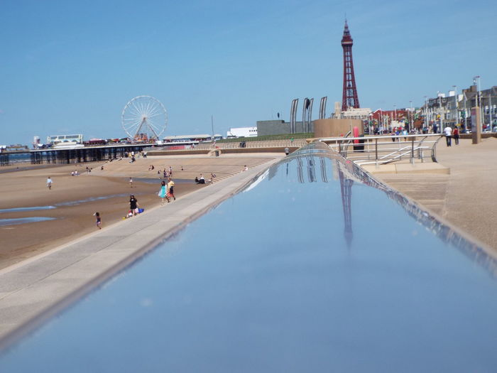 Reflection of Blackpool Tower on the top of the railingBlackpool Tower Blue Sky Blackpool Beach Metal Structure The Essence Of Summer Summertime Summer 2016 Tourist Attraction  Sightseeing Playing In The Sand Tourists People On The Beach Reflection Railing Blackpool Promenade People Of The Oceans
