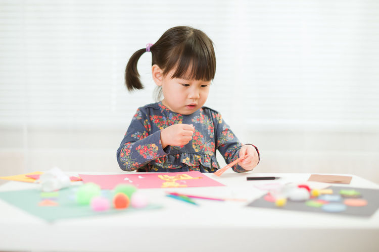 Girl playing at table against wall