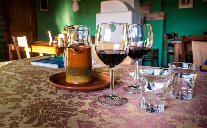 Glass of red wine on a table in rustic restaurant Refreshment Drink Alcohol Table Food And Drink Glass Wine Wineglass Indoors  Freshness Glass - Material Transparent Drinking Glass Still Life No People Household Equipment Restaurant Business Close-up Food Red Wine Rustic