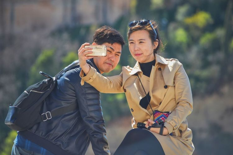 Young couple clicking selfie with smart phone outdoors