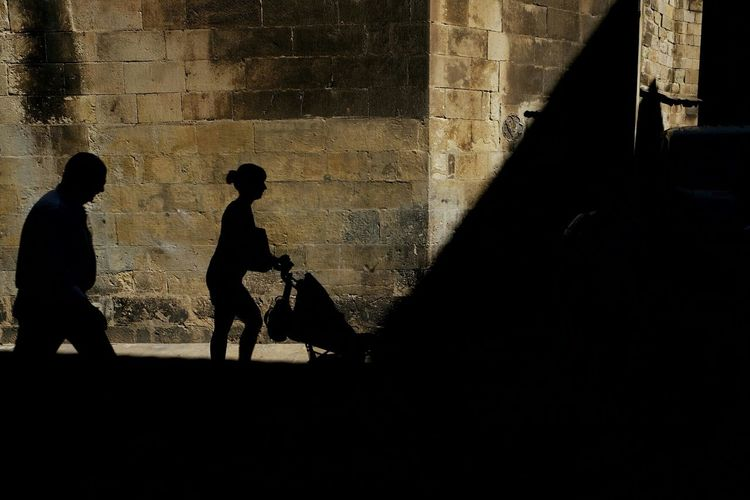 Silhouette of woman against wall
