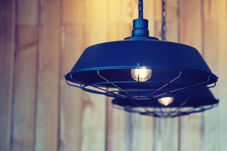 Close-up of illuminated light bulb hanging on wall