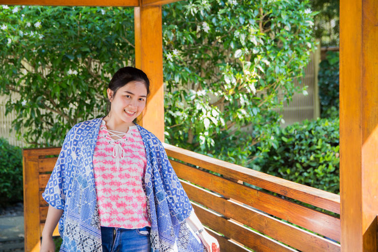 Portrait of smiling young woman standing at gazebo