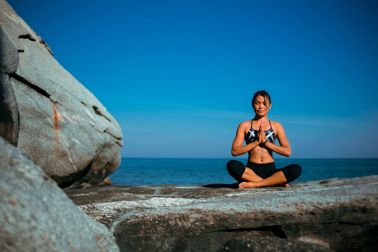 Young woman practicing yoga on rock at beach against blue sky
