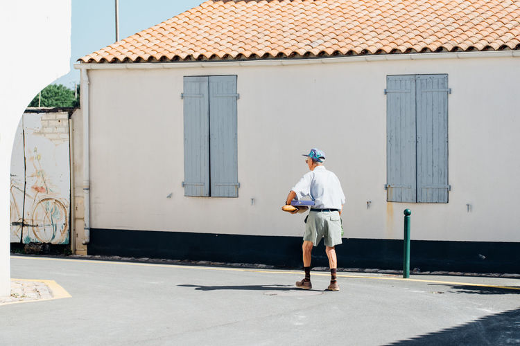 Rear view of man walking on road by house during sunny day