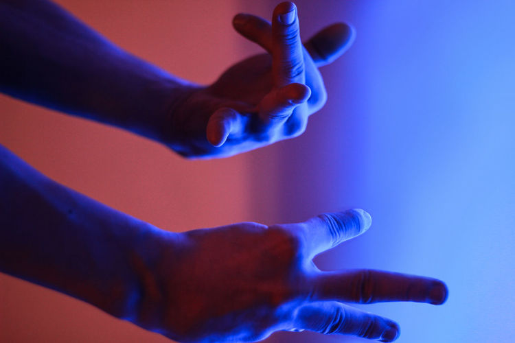 Cropped hands of person gesturing in illuminated room
