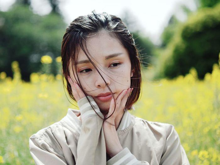 Portrait of beautiful woman on field
